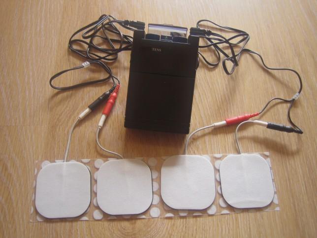 Appareil d'électrothérapie (TENS) relié à 4 électrodes